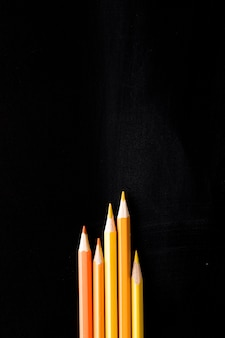 Yellow pencils on black desk
