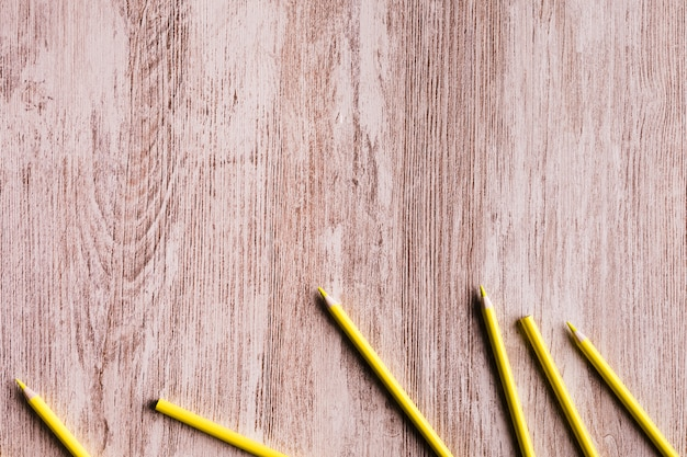 Yellow pencils on wooden surface