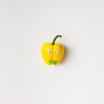 눈과 흰 벽에 bowtie와 노란색 고추. 최소한의 개념