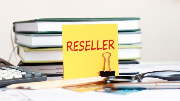 Желтый лист бумаги с текстом реселлера стоит на зажиме для бумаг на столе на фоне сложенных книг, калькулятора, кредитных карт. бизнес и финансовая концепция. выборочный фокус.