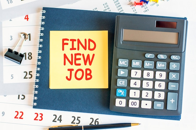 텍스트가있는 노란색 종이 조각이 새 일자리를 찾고 계산기가 메모장에 누워 있습니다. 노트와 펜이 문서 페이지에 배치됩니다. 비즈니스 및 금융 개념. 선택적 초점