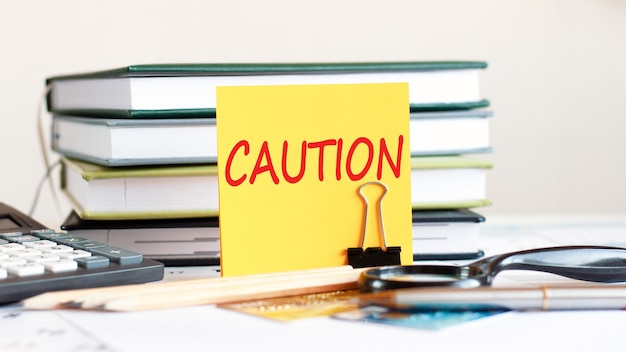 Yellow piece of paper with text caution stands on a clip for papers on the desk against books stacked, calculator, credit cards. business and financial concept. selective focus.
