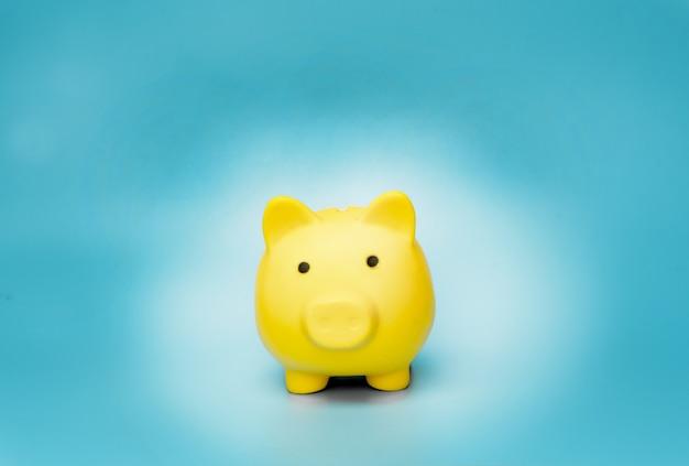 青い背景に黄色の貯金箱