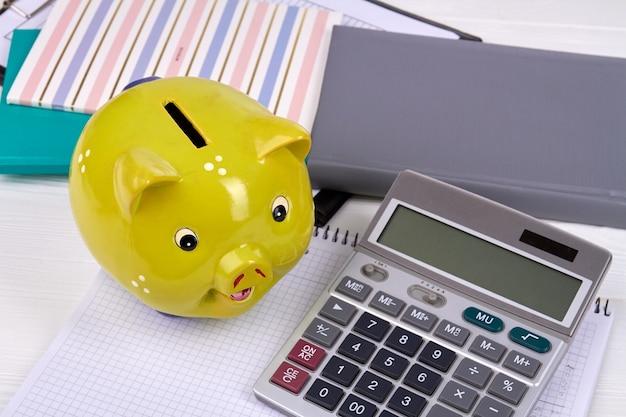 電卓とコピー本の黄色の貯金箱。