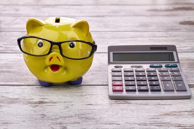 Желтая копилка с очками и калькулятором на деревянном столе