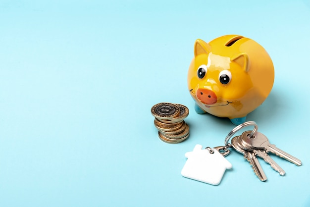Yellow piggy bank with keys on copy space background