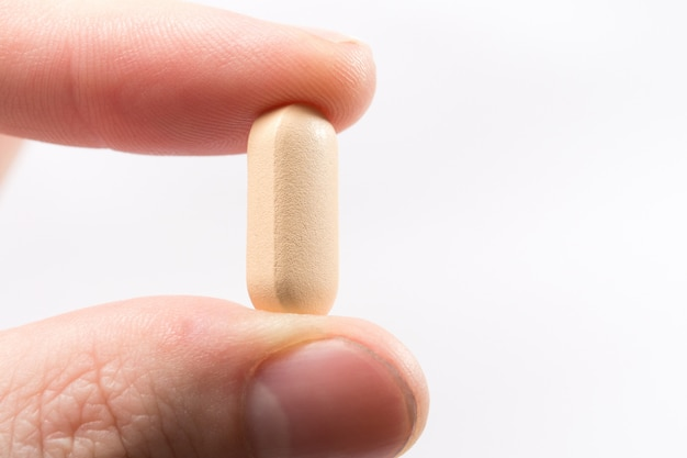 Yellow pill in a hand