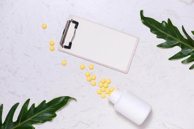 테이블에 노란색 알 약과 빈 노트북입니다. 플랫 레이.