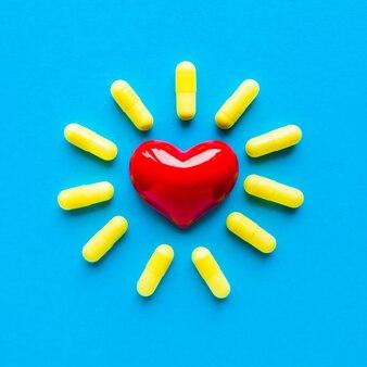 赤いハートの周りの黄色い錠剤は、青い背景のボトルから落ちました。フラットレイ、上面図。平方