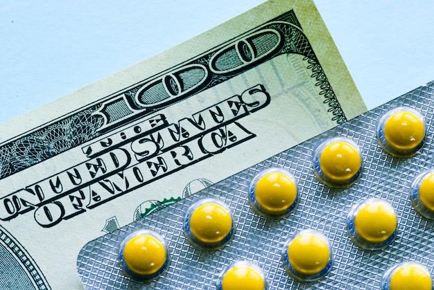 Yellow pills in blister on cash money
