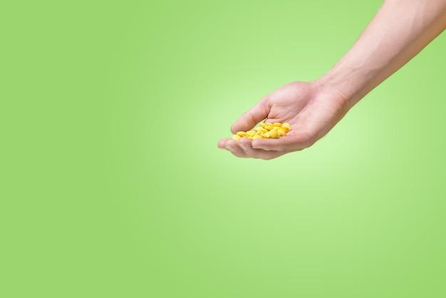 緑の背景に手に黄色の錠剤。