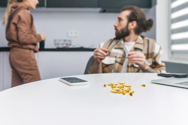 Желтые таблетки лежат на столе на фоне молодых супругов