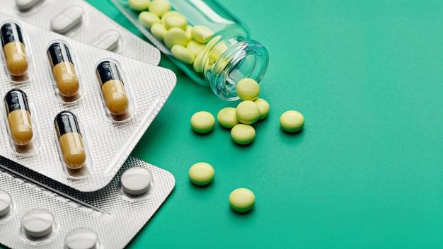 Желтые таблетки разбросаны из бутылки на зеленом фоне. фармацевтическая индустрия. аптека.