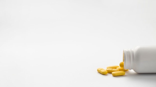 Yellow pills spilled from bottle isolated over white background