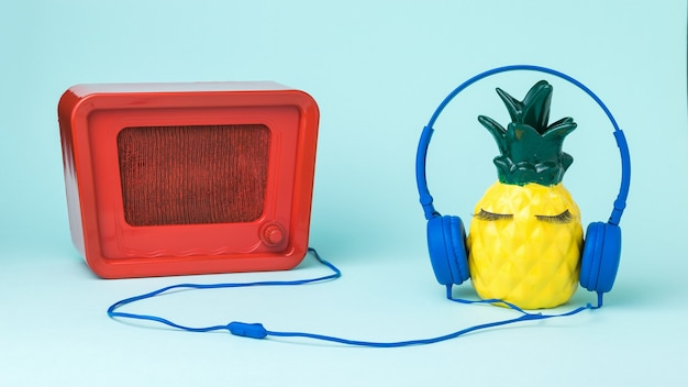 Yellow pineapple in blue headphones listens to a retro radio. the concept of global digitalization.