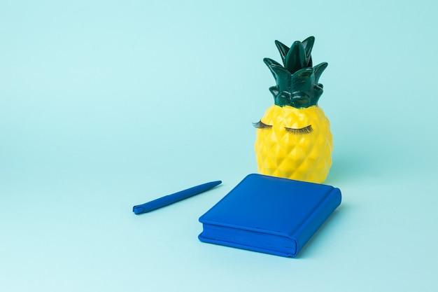 노란색 파인애플, 파란색 노트북 및 파란색 배경에 펜. 기록 보관의 개념.