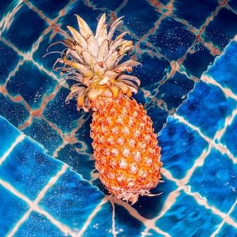 Желтый ананас, плавающий в бассейне. минимальный