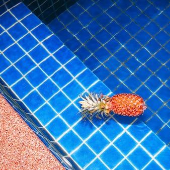 Желтый ананас плавает в бассейне. минимальный