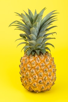 A yellow pineapple isolated on yellow. creative tropical fruit concept