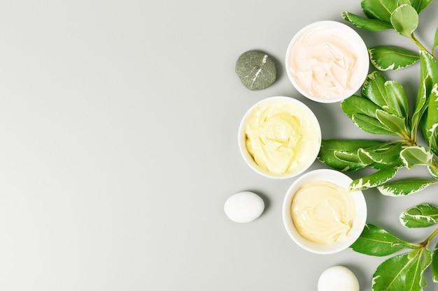 灰色の背景に黄色、ピンク、ベージュのクリームと緑の葉。ビューティーサロンと自然化粧品のコンセプトです。トップビュー、フラットレイアウト、コピースペース。