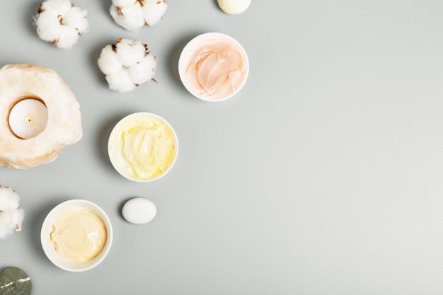 黄色、ピンク、ベージュのクリーム、キャンドル、灰色の背景に綿。自然化粧品と美容のコンセプト。