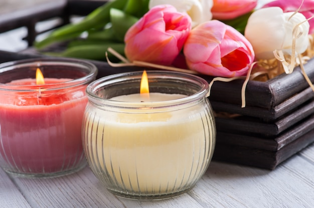 Yellow and pink aroma candles with tulips