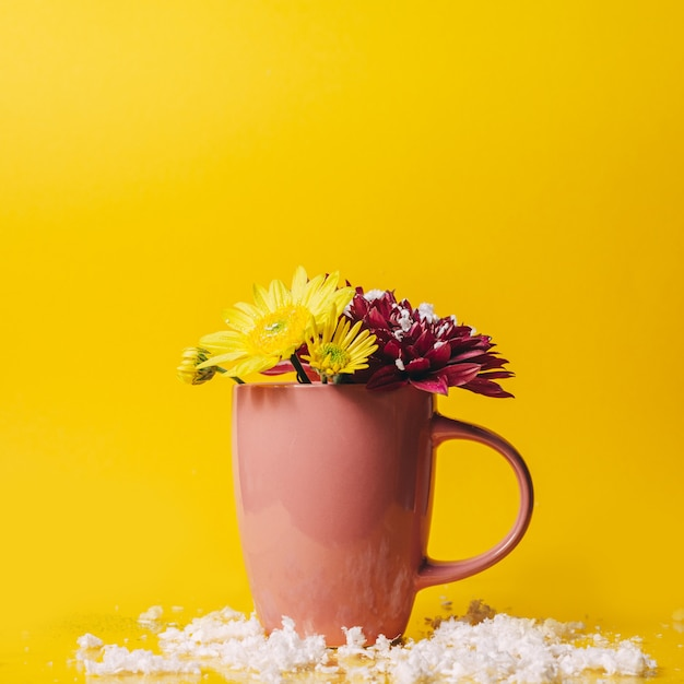 Yellow and pink gerbera flowers in a pink cup on a yellow background