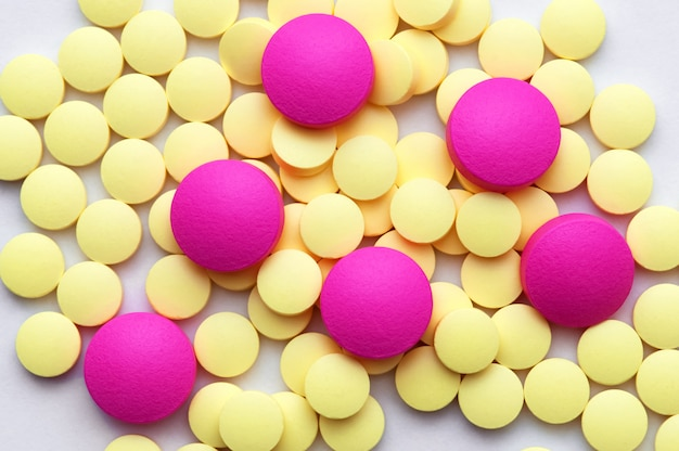 Yellow and pink pills on a white background.