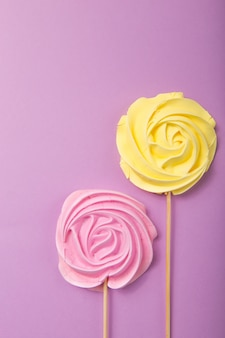 Yellow and pink rose candy   in pastel colors on a wooden stick on a grey  background