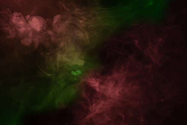 Yellow and pink steam on a black background. copy space. Premium Photo