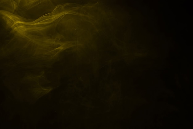 Yellow and pink steam on a black surface. copy space.