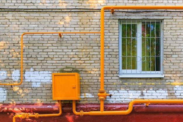 Желтые трубы газового хаба на фасаде жилого дома