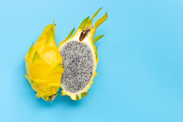 Yellow pitahaya or dragon fruit on blue background. copy space