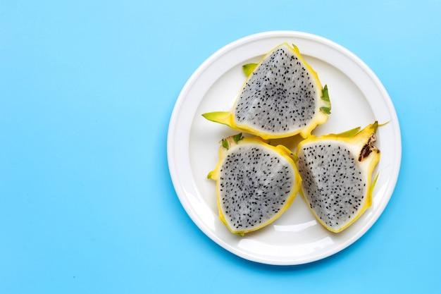 Yellow pitahaya or dragon fruit on white plate