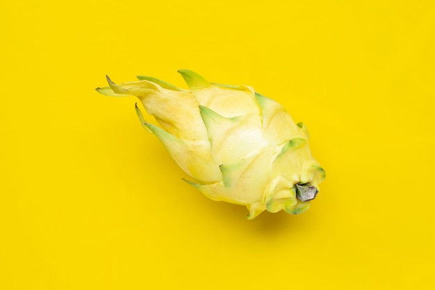 Yellow pitahaya or dragon fruit on yellow background. copy space