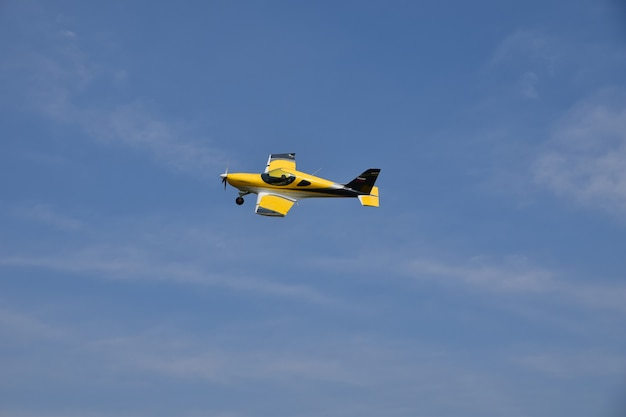 Yellow plane soars in the sky