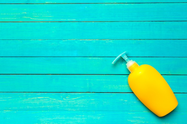 Yellow plastic bottle of sunscreen protection cosmetic lotion on bright background