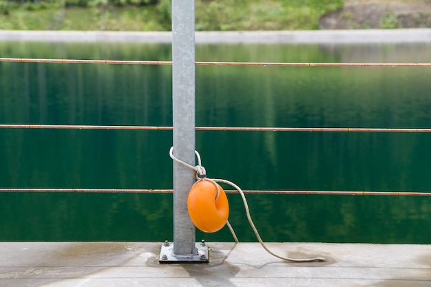 Yellow plastic buoy attached to a metal fence on the bank of a lake with green water.