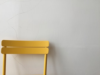 Yellow plastic chair against a white wall