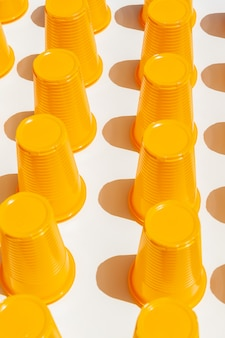 Yellow plastic drinking cups in rows