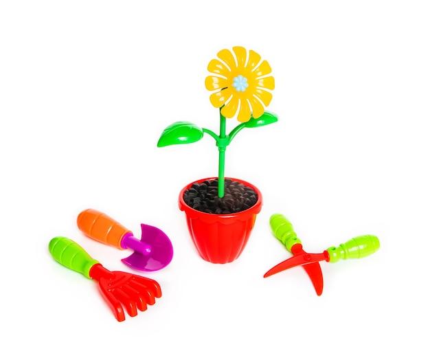 Желтый пластиковый цветок в красном горшке на белом фоне. садовые инструменты. детские игрушки.