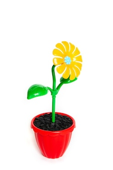 Yellow plastic flower in the red pot isolated on white background
