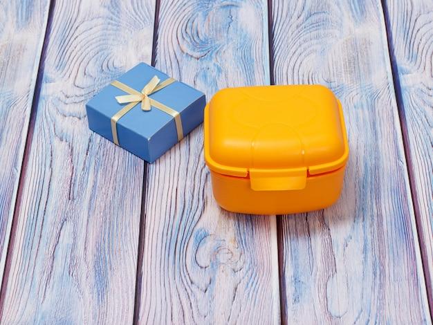 Желтый пластиковый ланч-бокс и подарочная коробка на деревянном фоне. вид сверху.