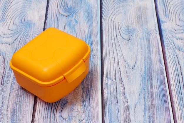 Желтый пластиковый ланч-бокс на деревянном фоне. вид сверху.