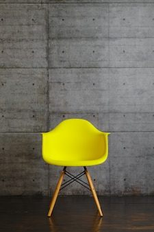 Yellow plastic modern design armchair on wooden stands