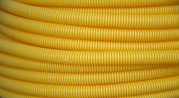 黄色のプラスチックポリ塩化ビニールフレックスパイプテクスチャ背景