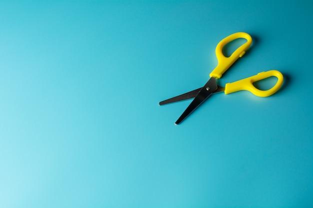 Yellow plastic scissors on blue paper