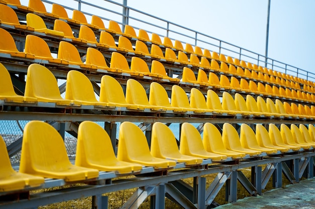 Yellow plastic seats on the podium of a small sports field