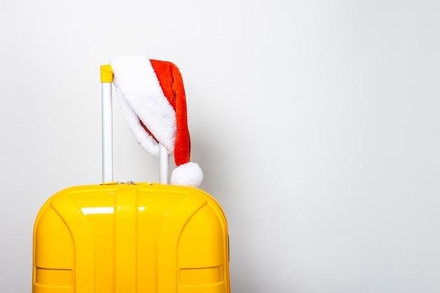 Желтый пластиковый чемодан в красной шапке санта-клауса