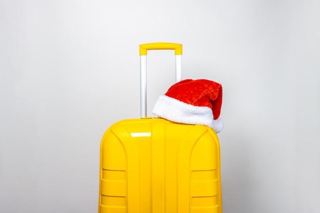 赤いサンタクロースの帽子をかぶった黄色のプラスチック製スーツケース